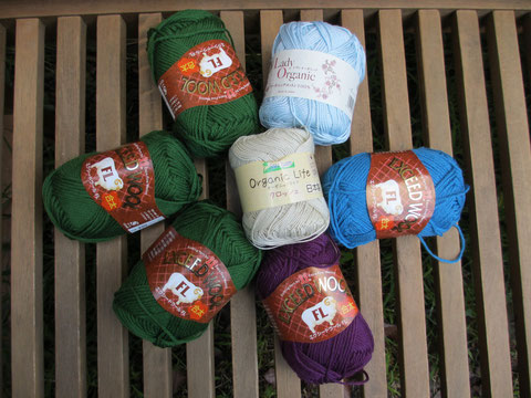 A collection of seven balls of yarn: three green, one blue and one purple all of the same brand, plus a pale blue cotton and a natural brown thin cotton.