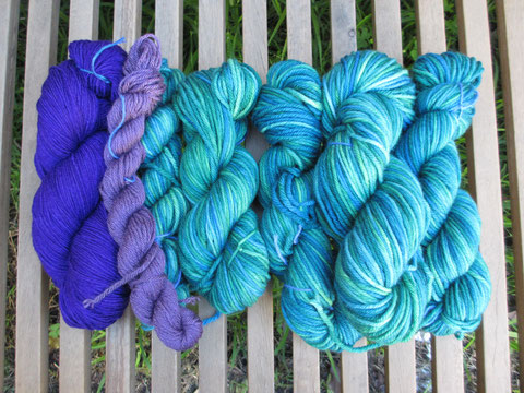 Wound up skeins of yarn, in green and purple
