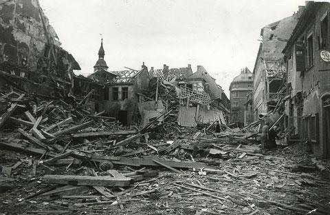 Kriegszerstörungen auf beiden Seiten der Gasse 1944. Im Hintergrund das Bavaria-Kino.