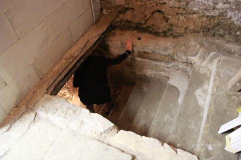 Durch eine enge Öffnung im Boden des ersten Kellers führt die erste Treppe hinab