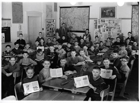 Friedenschule (Ludwigschule) 1958 oder 1959 - Lehrer: Leitherer - an der Türe sitzend links, Buch hochhaltend Peter Hofmann, zwei weiter links sitzend: Joachim Hoffmann;
