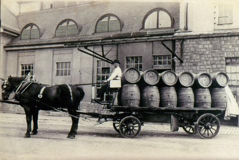 Erstes Rappengespann mit Bierführer Nikolaus Bienert (Eintritt 1925) auf dem Brauereihof, beladen mit Doppel-Hektoliter und Ein-Hektoliter-Fässern