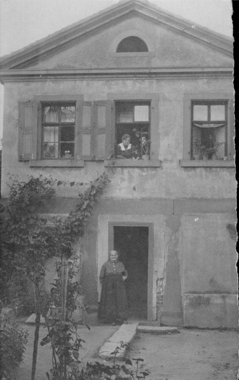 """Friedrich-Ebert-Str. 1 (heute steht hier das Naturfreundhaus, damals eine andere Anschrift) hinter dem Haus befand sich der """"Bockstall"""", der von Frau Elisabeth Grimmer """"verwaltet"""" wurde (in der Türe); oben Hulda Jobst (ca. 1895)"""