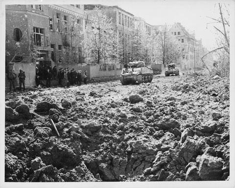 Die amerikanische 12. Division der 7. Armee marschiert am 11. April in der Ludwigstraße in Schweinfurt ein. Links befreite russische Zwangsarbeiter.