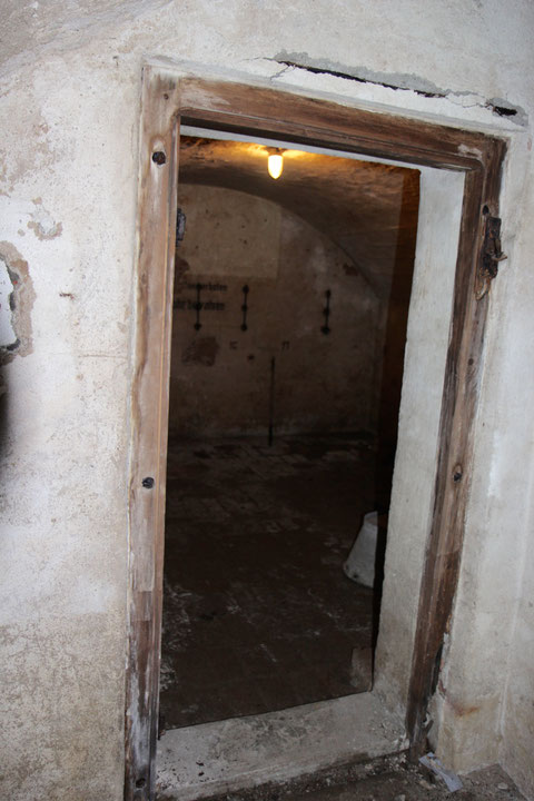 Luftschutzdurchgang in den unteren Keller - hier an der Wand die Platznummerierungen bei Aufenthalt während eines Bombenangriffs