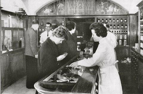 Die Apotheken-Offizin um 1962 mit Herrn Apotheker Wilhelm Faustmann (links hinten)