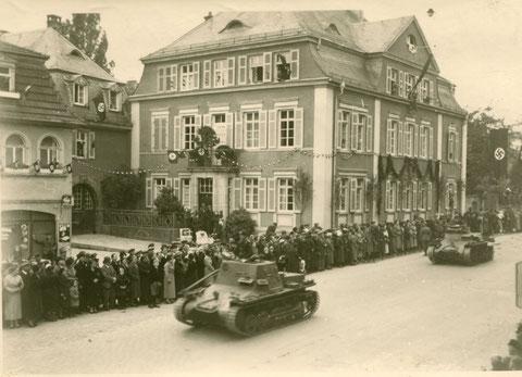 """1936 - die 4. Panzerdivision zieht ein, hier auf dem Weg zum Marktplatz an der Einmündung der Neuengasse mit Haus Kornmarkt 17 (links das """"Schnapslädele"""", heute Mangold)"""