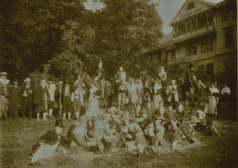 Umfangreiche kostümierte Gruppe auf der Kurparkwiese vor dem Felsenkeller lagernd - Quelle: Monika Reich   Foto vermutlich um 1910