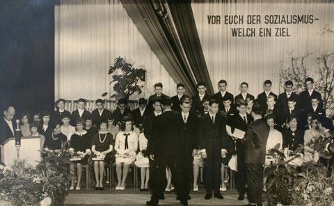 """Eberhard Müller (vorne rechts) erhält gerade sein """" Weltall, Erde, Mensch - Buch"""" , links spricht Physiklehrer Przybyszewski"""