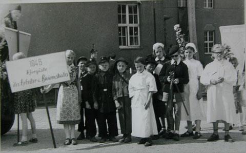 """Vorbereitung für einen Umzug 1957 auf dem """"Oberen Schulhof """" der späteren POS """"Rudolf Schwarz"""": Auf dem Schild steht: 1946 - Kurgäste des Arbeiter- und Bauernstaates"""