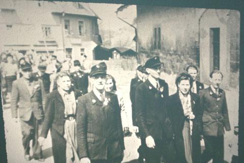 Rechts altes Brunnenhaus in der Theaterstr, links früherer Spielwaren-später Gemüseladen - Postler vermutlich Mitte bis Ende 1950er zur 1.Mai Demonstration, im Bild rechts von der Dame teilweise verdeckt -Josef Malek  - Archiv W.Malek