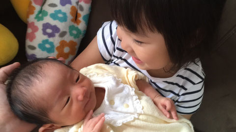 産まれた次女に微笑むお姉ちゃん