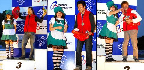 レースクイーンといっしょに喜びを噛みしめる各ライダーたち。左から3位/橋川選手、1位/新垣(急用で表彰式を欠席した新垣選手に替わり、壇上には代理の関根さんが登った)、2位/庭田選手