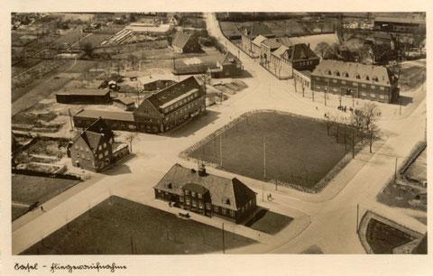 Auf dieser Postkarte, als Fliegeraufnahme gekennzeichnet, von 1931 sehen wir das Rathaus, im Hintergrund Mitte die Schule und rechts daneben die Post, beide Gebäude stehen heute noch unverändert.