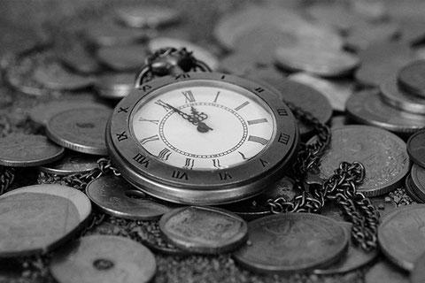Eine Taschenuhr auf einem Boden aus Münzen