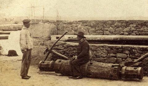 Deux marins discutent près du mur de la base du quai, l'un est assis sur un antique guindeau à barres comme le montre les trous carrés