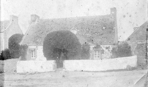 L'ancienne maison du capitaine Yves Floch, cette photo date d'avant 1910, un enfant joue au cerceau. Un grand buis ou un fusain encadre la porte, à droite le pignon du skiber