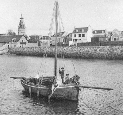 Dans le port du vil à Roscoff un joli sloup, à bord une femme avec la coiffe de l'île le patron et deux mousses.  Trois défenses en bois protègent la coque du ragage sur les pierres des cales