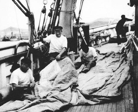 Les hommes d'équipage réparent les voiles