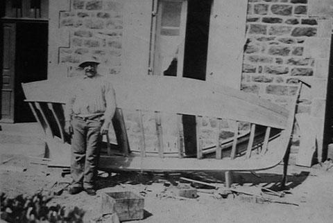 Adrien Briand, charpentier de marine de Ploumanac'h, construisant en plein air, devant chez lui, ici  un canot de 4,50 m