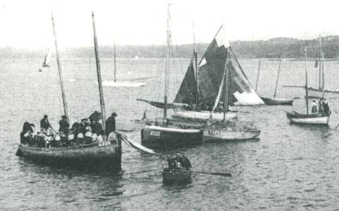 Aux régates de Perros vers 1900, 24 hommes avec des chapeaux et femmes en coiffe à bord du goémonier St Anne L100 de Louannec, mais celui jauge bien 6 ou 7 tonneaux