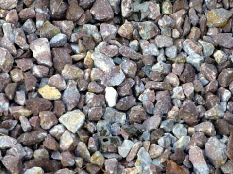 Verschiedene Kies- + Steinsorten in einem Metallrahmen gesammelt.