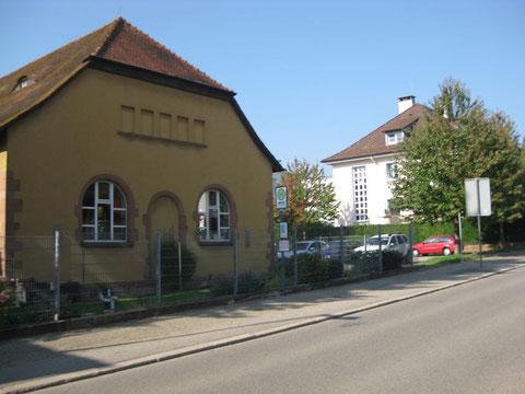 Sicht auf die Turnhalle (links gelbes Gebäude) und Einfahrt vom Parkplatz