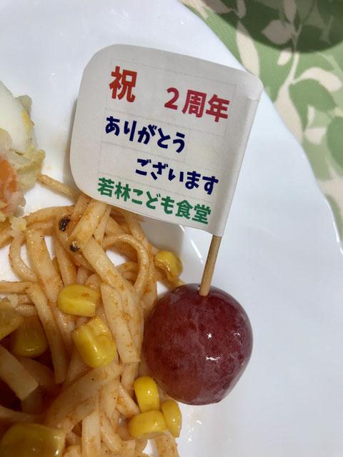 ☆お料理のプレートの真ん中にブドウに刺した楊枝の旗「祝 2周年 ありがとうございます 若林こども食堂」。