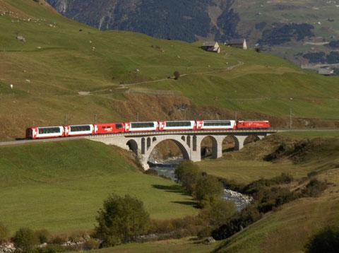 Eine HGe 4/4 vorgespannt an einer Premium-Garnitur des Glacier Express im Urserental vor Hospenthal.