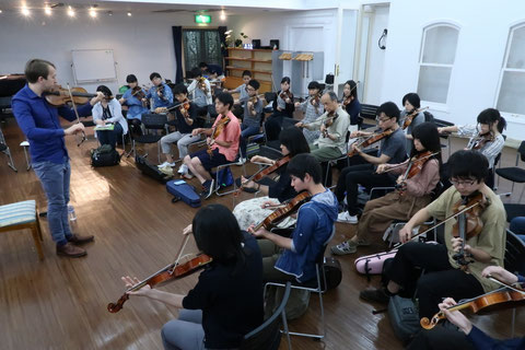 Oisin MacDiarmada teaching the fiddle at a workshop in Tokyo