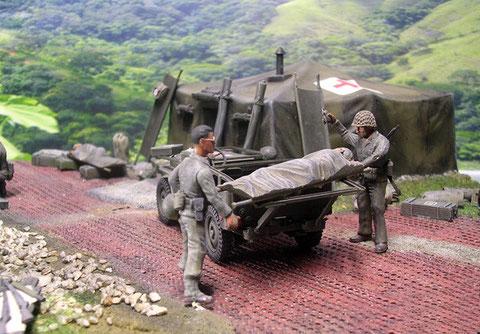 Die Verwundeten werden am Tropf hängend vom Jeep abgeladen.