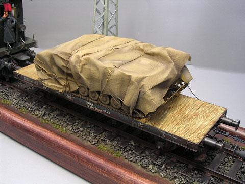 Panzerfahrgestell auf Tieflader, verzurrt und mit Keilen gesichert.