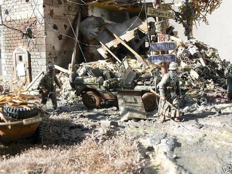 Vorbei an verlassenen US Jeeps und einem dramatischen Trümmerberg.