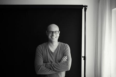 Porträtfoto Mirko Kussin vor schwarzem Fotostudio-Hintergrund. Lacht in die Kamera.