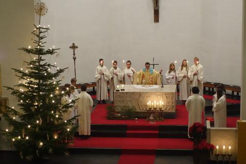 Pfarrer und Ministranten um den Altar versammelt während einer Messe