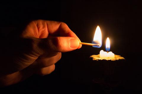 Kurze, weiße Kerze anzünden mit Zündholz