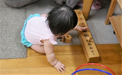 11ヵ月のお子様がモンテッソーリの個別活動ではめ込み円柱に興味を持って、取り組んでいます。