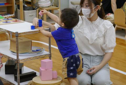 モンテッソーリの個別活動で、お母さまがお子様の活動を見守りながら援助しています。