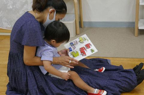 モンテッソーリの個別活動で、お母さまがお子様にやさしく絵本の読み聞かせをしています。