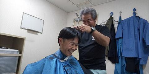 しらせの理髪室で上陸前の散髪。かみを切っているのは野外安全管理担当の小久保さん。
