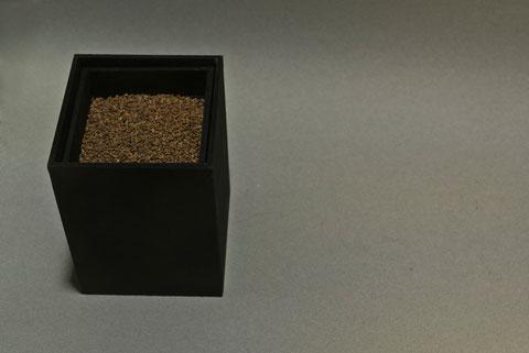 Caja Órgano, 2014. Caja doble de madera pintada de negro, que contiene un mecanismo que hace vibrar a las piedras situadas en el receptáculo superior. 12 x 9 x 9 cm.