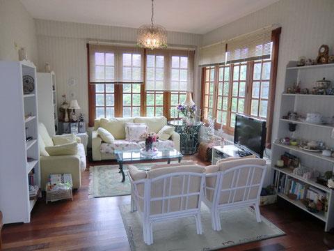Das 2. Wohnzimmer ist mit hellen Möbeln und grosser Fensterfront.