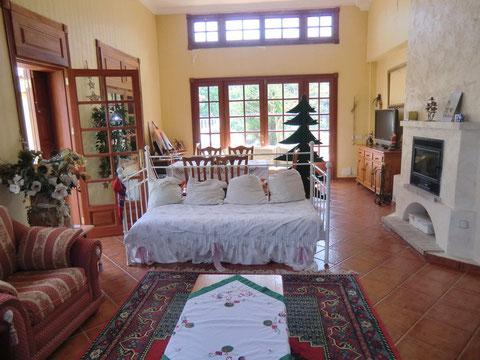 Grosses Wohnzimmer unterteilt in Essbereich und gemütlichen Wohnbereich mit Kamin und direktem Zugang zum Garten