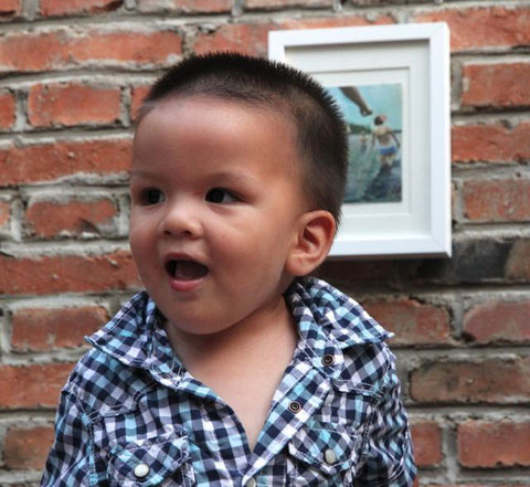 little Hakim happily in front of my open studio painting