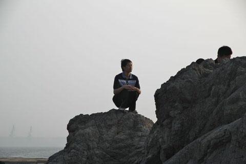 Dieser junge Mann, der da so andächtig auf dem Stein sitzt, post gerade für seine Freundin.