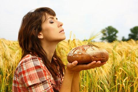 Frau im Kornfeld mit duftendem frischen Brot