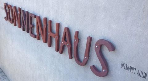 PD - 2012 - Entwurf Schriftzug SONNENHAUS (Fassadenaufschrift) - Buchstaben aus Keramik, hochgebrannt und unbehandelt (pro mente, TS Keramik, Linz), Untergrund: geschliffener Sichtbeton, Befestigung: Messingschrauben