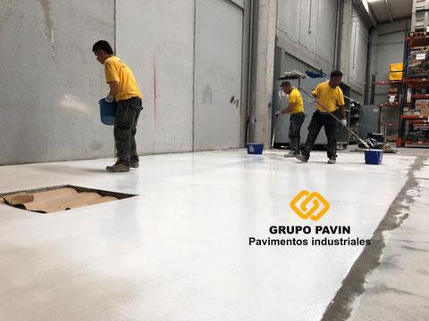 Primera capa y espolvoreo a saturación en los suelos de resina para el pavimento industrial epoxi bicapa base agua transpirable