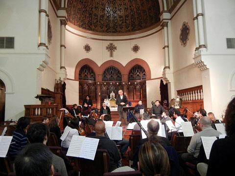 公演前日の練習で米国側のオケ、合唱団に挨拶する長谷川・東京アカデミー合唱団代表