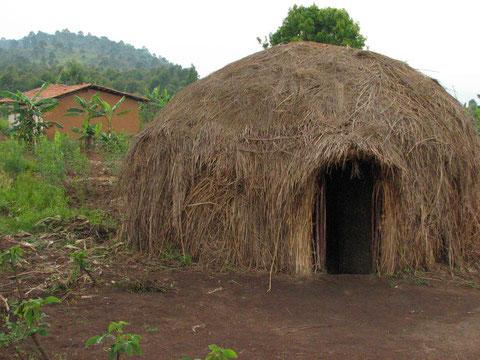 Tipica capanna Batwa con sullo sfondo una nuova casa.